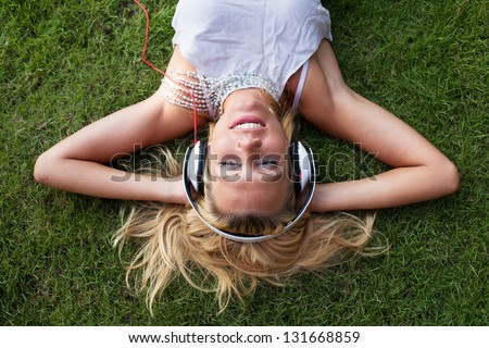 smiling woman in headphones on the grass