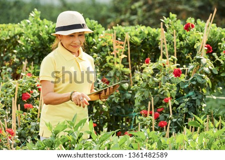 Smiling woman in her garden #1361482589
