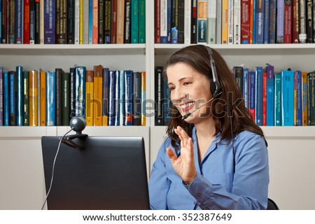 Smiling woman in her office with laptop, camera and headset telephoning with her children via the internet