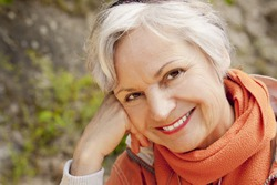 smiling woman in her 60s outdoors