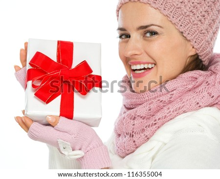 Smiling woman in knit winter clothing holding Christmas present box
