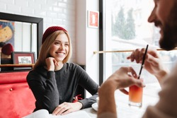 Smiling Woman in red hat talking with man by the table in cafe
