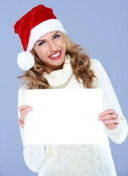 Smiling woman in Santa hat holding blank board with copyspace