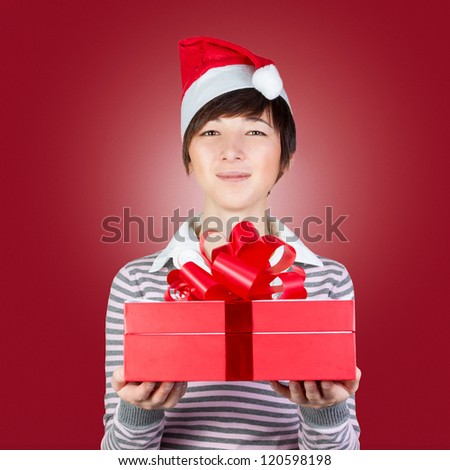 Smiling woman in Santa hat with gift box on red background