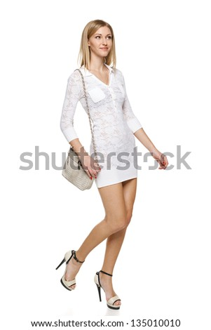 Smiling woman in white lacy dress with small handbag in full length walking over white background