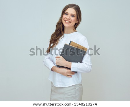 smiling woman in white shirt holding book. isolated portrait.