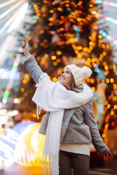 Smiling woman in winter style clothes posing with christmas star in Christmas market decorated with holiday lights in the evening. Lights around. Winter holiday.