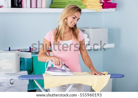 Smiling Woman Ironing Clothes Using Iron On Ironing Board After Laundry At Home
