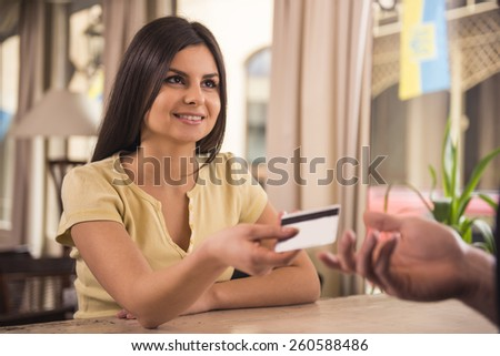 Smiling woman is paying for coffee by credit card.