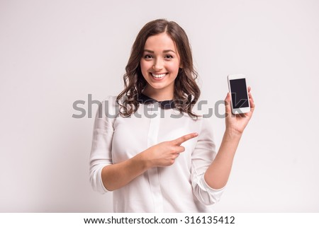 Smiling woman is pointing on smartphone standing on white background.