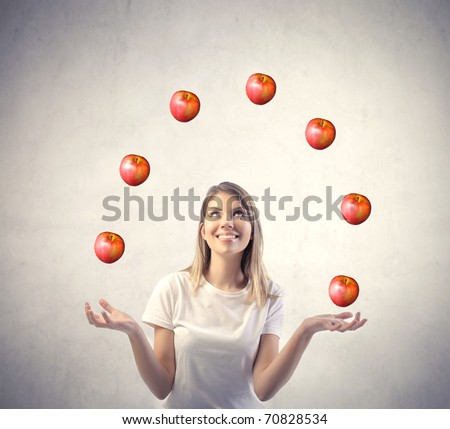 Smiling woman juggling with apples
