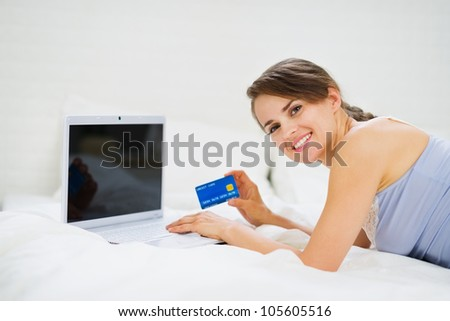 Smiling woman laying on bed with laptop and shopping on net