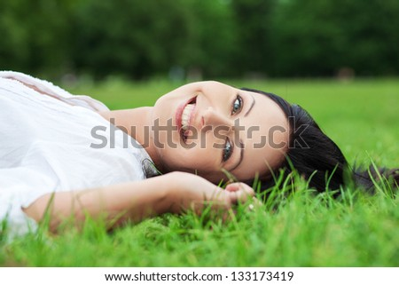 Smiling woman laying on grass - stock photo