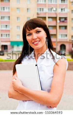 smiling woman leaning against a laptop