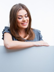 Smiling woman leaning on big blank board . Close up female face portrait with arms looking down.