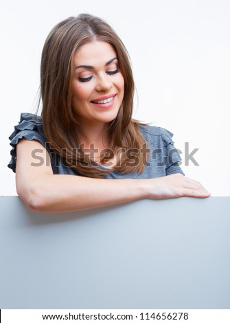 Smiling woman leaning on big blank board . Close up female face portrait with arms looking down. - stock photo