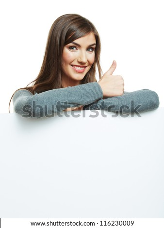 Smiling woman leaning on big blank board . Close up female face portrait with arms on blank card. Thumb up.