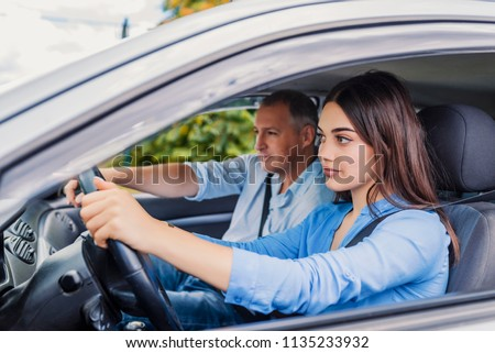 Smiling woman Learns to Drive in Car with instructor. Learning to Drive . Student driver taking driving test. Woman taking driving lessons from instructor #1135233932