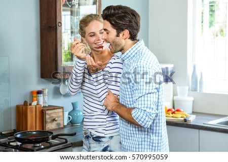Smiling woman letting man taste a sauce with a wooden spoon in kitchen at home
