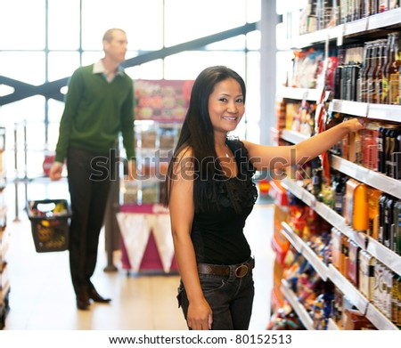 Smiling woman looking at camera with man in the background in shopping store