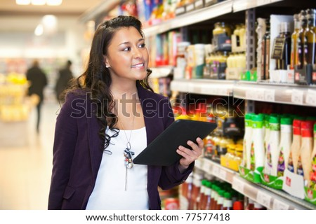 Smiling woman looking at the products while holding digital tablet with people in the background