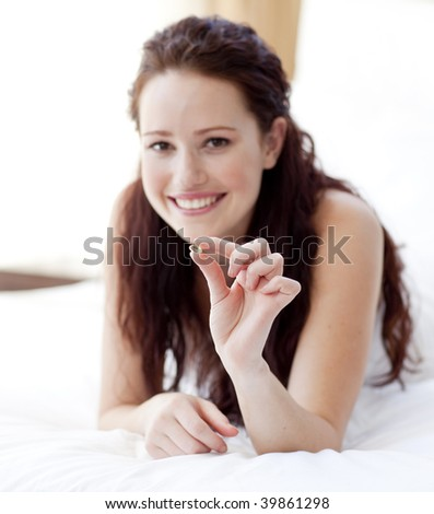 Smiling woman lying in bed holding a pill