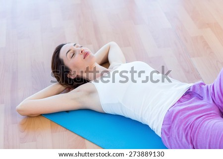 Smiling woman lying on exercise mat in medical office