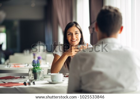 Smiling woman on a date in a restaurant,having a conversation over a meal in hotel.Cheerful female customer drinking coffee with a partner.Positive emotions,love,affection.Public place behave manners