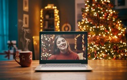 Smiling woman on a videocall, she is happy and wishing a merry Christmas online, Christmas tree and decorated room interior in the background