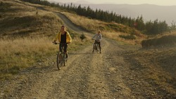 Smiling woman on bicycle looking back at man. Female and male bicyclists exercising in mountain landscape. Happy couple on bikes riding on road