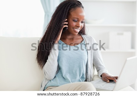 Smiling woman on sofa with smartphone and laptop