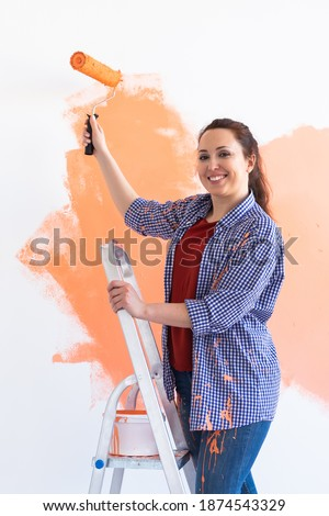 Smiling woman painting interior wall of home. Renovation, repair and redecoration concept. Foto stock ©