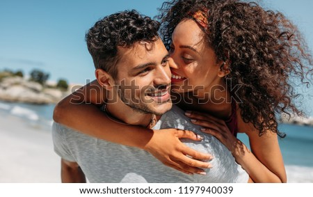 Photo of  Smiling woman piggy riding on her boyfriend and kissing him. Man carrying his girlfriend on his back outdoors.