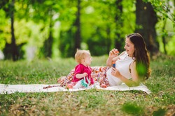 Smiling woman play and sit on green grass in park, rest and hug hold soap bubble blower with little cute child baby girl. Happy mother and daughter in the park. Family outdoor recreation.