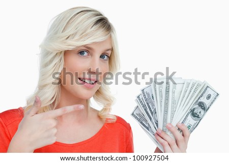 Smiling woman pointing at her dollar notes against a white background