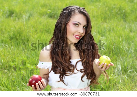 Smiling woman present apples in the garden