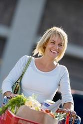 Smiling woman pushing shopping trolley in supermarket car park