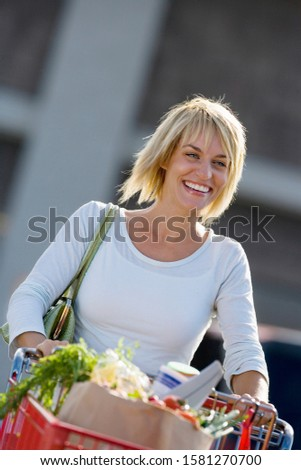 Smiling woman pushing shopping trolley in supermarket car park