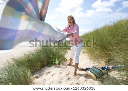 Smiling woman putting picnic blanket on sand dunes by beach
