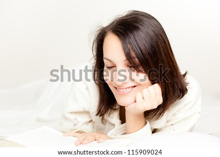 Smiling Woman Reading a Book on Bed