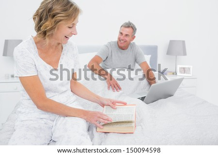 Smiling woman reading book while husband is using laptop in bedroom at home