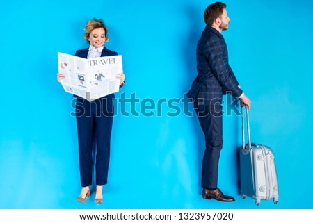 Smiling woman reading newspaper while man standing with valise on blue background