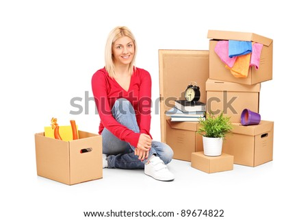 Smiling woman resting from moving into a new home with many boxes around her