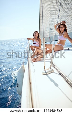 Smiling woman sailing on yacht - vacation, travel, sea, friendship and people concept #1443484568