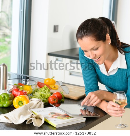 Smiling woman searching recipe tablet kitchen cooking food vegetables