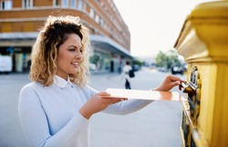 Smiling woman sending a letter and documents via mailbox. Business, lifestyle concept