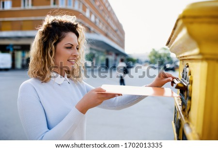 Smiling woman sending a letter and documents via mailbox. Business, lifestyle concept Stockfoto ©