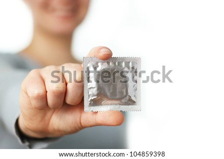 smiling woman shows a condom