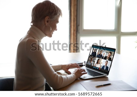 Smiling woman sit at desk have Webcam conference with diverse colleagues at home, businesswoman speak talk on video call with coworkers on online briefing or consultation using Webcam on laptop