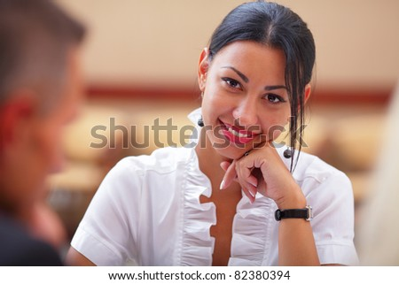 Smiling woman sitting at a business meeting with colleagues in office